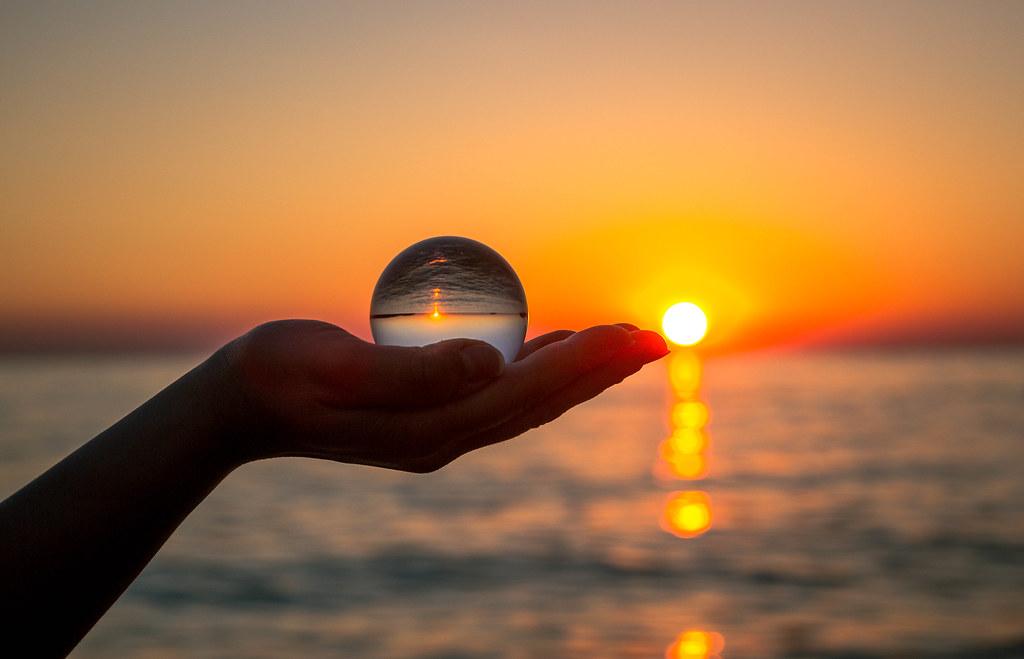 A glass palantir thru an ocean sunset
